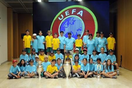 Crianças tiram uma fotografia com o troféu da UEFA Champions League, na sede da UEFA (©UEFA)